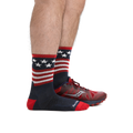 Profile of male legs facing to the right wearing Patriot Micro Crew Ultra-Lightweight Running Socks in Stars and Stripes and back foot wearing a running shoe