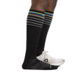 Profile image of a woman's legs on a white background wearing Women's Stride over the Calf Ultra-Lightweight Running Socks in Black with one foot also in an athletic sneaker