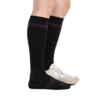 Profile image of a woman's legs on a white background wearing Women's Element Over the Calf Lightweight Athletic socks in Black with an athletic shoe on one foot