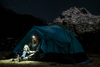 Hiker sitting in her tent, at night, with a headlamp on taking off her boots wearing women's stripes micro crew hiking sock in aqua stripe, Lifestyle Image