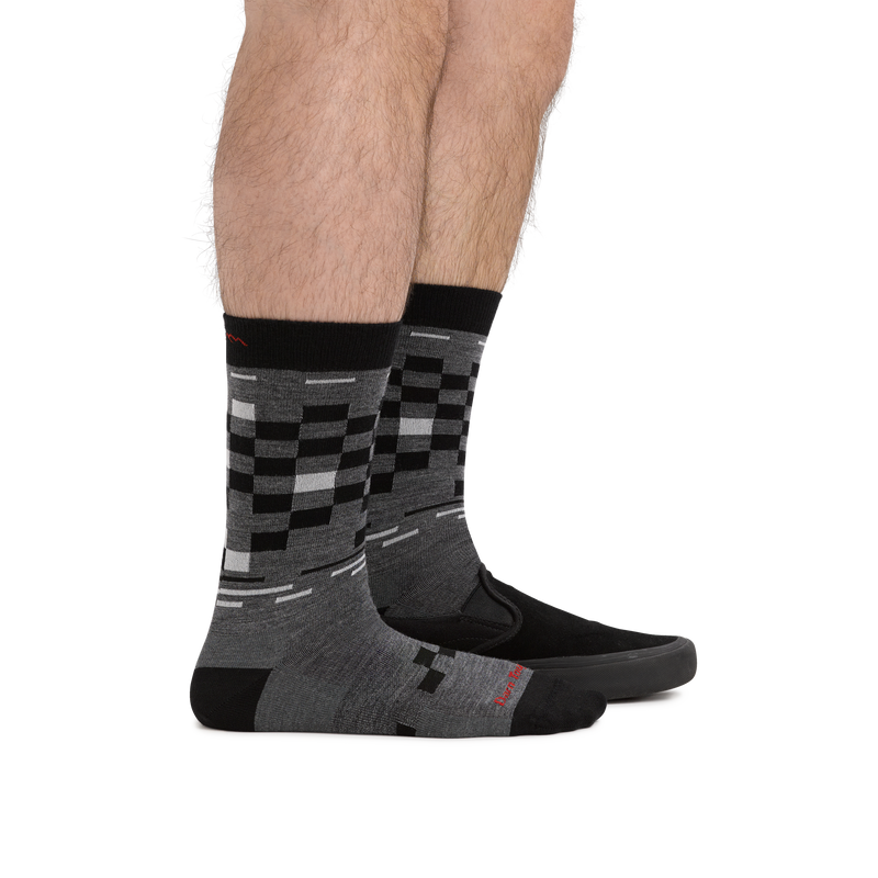 Waist down image of man facing to the right, wearing Derby Crew Lightweight Lifestyle Socks in Gray, front foot barefoot and back foot in a black shoe