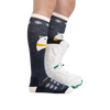Profile image of a woman's legs, facing right, wearing Women's Mama Bear Over the Calf Midweight Ski & Snowboard Socks in Blue with a snowboard boot on one foot