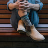 Image of a woman sitting on a bench, hugging her knees wearing boots and Women's Vines Crew Lightweight Lifestyle Socks in Taupe, Lifestyle Image