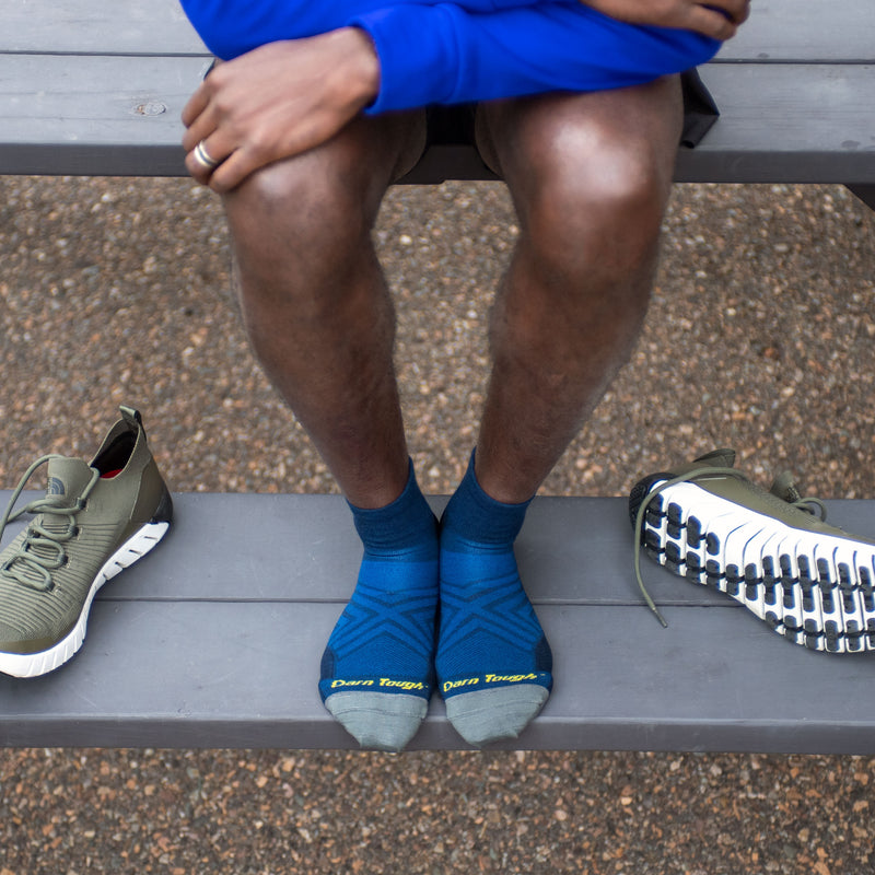Close up lifestyle image looking down at a man's legs while he is sitting on top of a picnic table, his feet on the bench with running shoes next to him wearing Run Quarter Ultra-Lightweight Running Socks in Baltic, Lifestyle Image