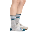 Profile image of a woman's legs on a white background, facing right, wearing Women's Pacer Micro Crew Ultra-Lightweight Running Socks in Ash with a sneaker on the other foot