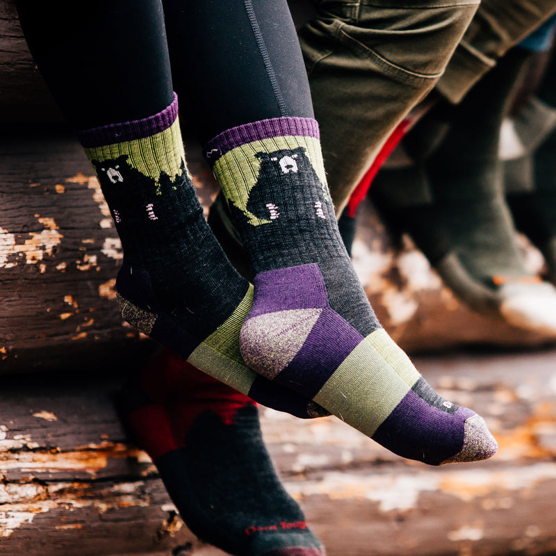 Close up image of a woman's feet, crossed at the ankles wearing Women's Bear Town Micro Crew Lightweight Hiking Socks in Lime, Lifestyle Image