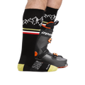 Man standing facing to the right, wearing Alpenglow Over the Calf Ski & Snowboard socks in Black, front foot with only sock on and back foot wearing a ski boot, showing the height of the sock comes to above the top of the ski boot