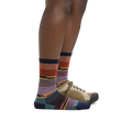 Profile image of a woman's legs in front of a white background, facing right, wearing Women's Pixie Crew Lightweight Lifestyle Socks in Navy with one foot in a casual shoe