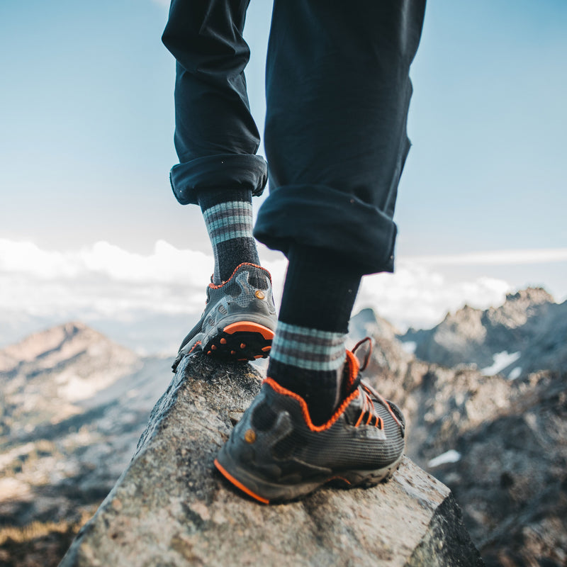 Close up lifestyle image of a man's feet standing at the edge of a rocky outcropping, looking over a mountainous vista wearing hiking shoes and Spur Boot Lightweight Hiking Socks in Charcoal, Lifestyle Image