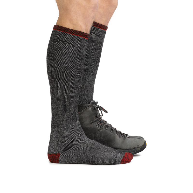 Profile of male legs wearing Mountaineering Over the Calf Heavyweight Hiking Sock in Smoke, back foot wearing a hiking boot