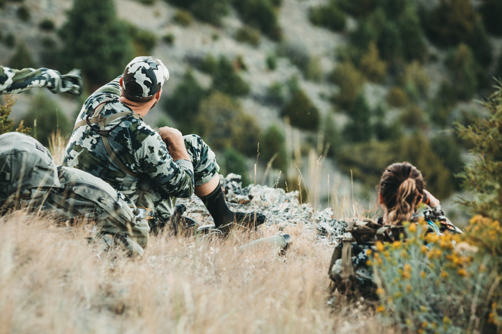 Man and woman sitting in the tall grass on a ridge, looking out over the valley below wearing hunting boot socks in charcoal, Lifestyle Image