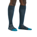 Image of a woman's legs on a white background wearing Women's RFL Over the Calf Ultra-Lightweight Ski & Snowboard Socks in Dark Teal
