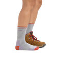 Image of a woman's legs facing right on a white background wearing Coolmax Hiker Micro Crew Midweight Hiking Socks in Light Gray with one hiking boot on the back foot