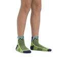 Kid standing barefoot wearing Hiker Quarter Lightweight Hiking socks in Green with foot in rear also wearing a hiking boot