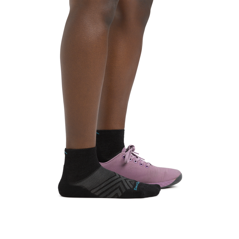 Profile image of a woman's legs on a white background, facing right, wearing Women's Run Quarter Ultra-Lightweight Running Socks in Black with a running shoe on one foot