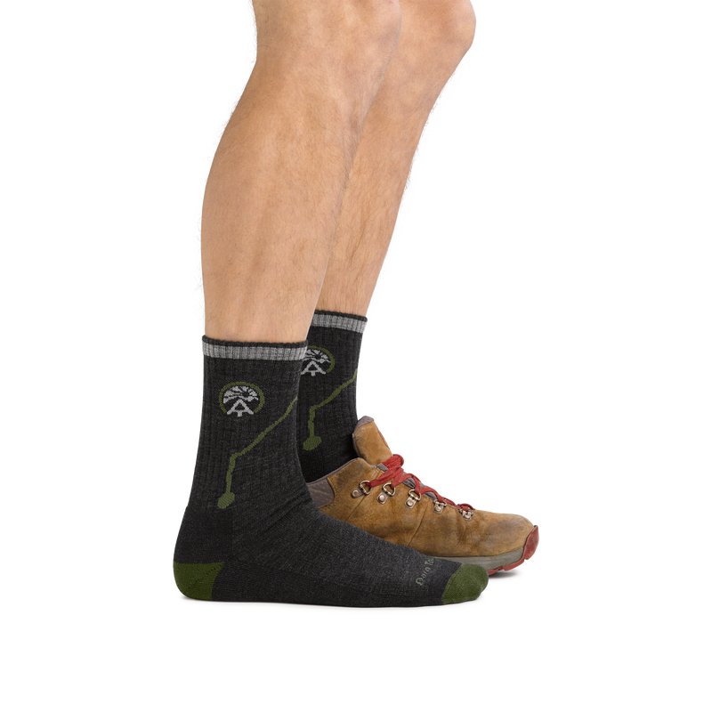 Man standing, facing right, front foot wearing only ATC Micro Crew Hiking sock in Charcoal, back foot in a hiking boot, showing that the sock rises to mid-shin, above the top of the boot