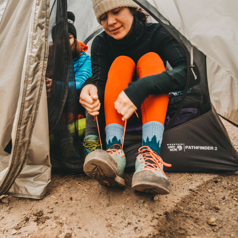 Female hiker tying her shoes at the front of her tent getting ready for the day, wearing women's treeline micro crew hiking sock in blue, Lifestyle Image