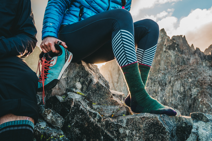 Image of a woman sitting on the rock face of a mountain, holding her shoes in one hand while wearing Women's Hiker Micro Crew Midweight Hiking Socks in Moss Heather, Lifestyle Image