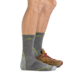 Profile of male legs facing to the right, front foot wearing Man standing barefoot wearing Light Hiker Micro Crew Lightweight Hiking Sock in Gray and back foot also in a hiking shoe