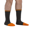 Man standing barefoot wearing Steely Boot Midweight Work Socks in Graphite