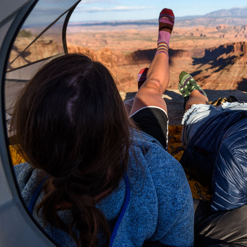 Two female hikers sitting in a tent, looking out over a desert canyon with one wearing stripes micro crew hiking sock in plum stripe, Lifestyle Image