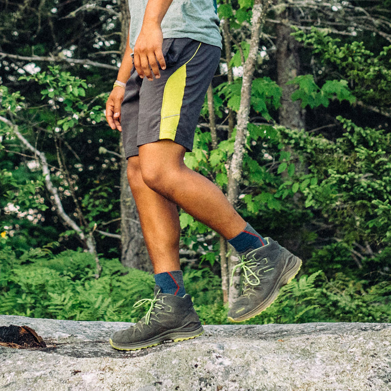 Image of a man hiking over a rock in the woods wearing hiking boots, shorts, and Men's Hiker 1/4 Socks in Denim, Lifestyle Image