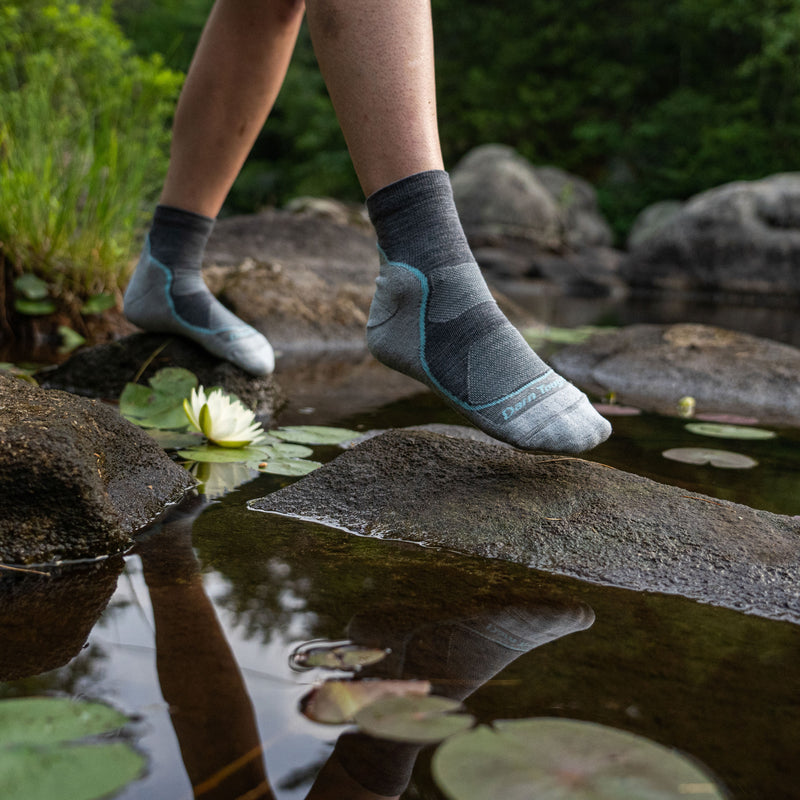 Image of a woman's feet, stepping on rocks surrounded by water and lily pads, wearing Women's Light Hiker Quarter Lightweight Hiking Socks in Slate, Lifestyle Image