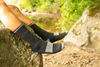 Close up of feet hanging off a rock wearing darn tough 1403 men's hiker boot hiking socks in black, Lifestyle Image