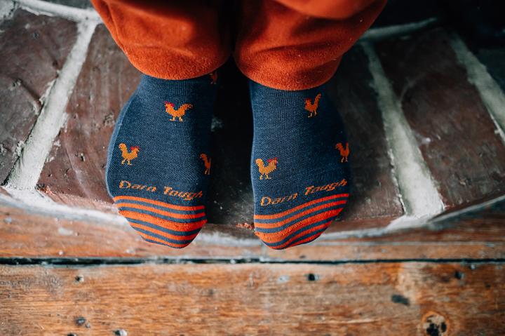 Close up lifestyle image looking down on the tops of a man's feet standing on a brick hearth wearing  Strut Crew Lightweight Lifestyle Socks in Dark Teal, Lifestyle Image