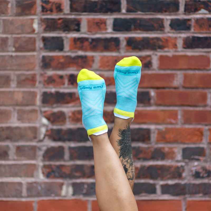 Image of a woman's legs up in the air in front of a brick wall wearing Women's Run Coolmax No Show Running Socks in Aqua, Lifestyle Image