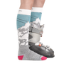 Image of a woman's legs on a white background, facing right, wearing Women's Yeti Over the Calf Ski & Snowboard Socks in Glacier with a ski boot on one foot