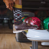 Close up image of man in a bowling alley wearing bowling shoes and pulling up his Derby Crew Lightweight Lifestyle sock in Charcoal, Lifestyle Image