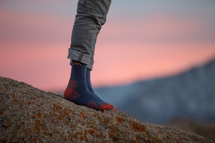 Close up Lifestyle Image of a man standing on a rock, with a pink sky sunset behind him wearing rolled cuff pants and Hiker Micro Crew Hiking Socks in denim