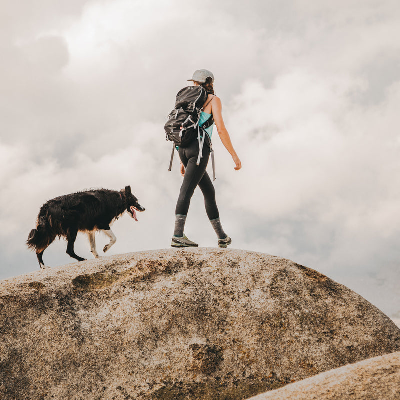Image of a woman hiking with her dog, walking along a rocky ledge wearing a hiking backpack, hiking shoes and Women's Hiker Boot Midweight Hiking Socks in Slate, Lifestyle Image