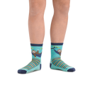 Kid standing barefoot wearing Lazy Daze Micro Crew Lightweight Hiking Socks in Aqua with toes pointed out so sloth pattern on front and inside of shin is visible