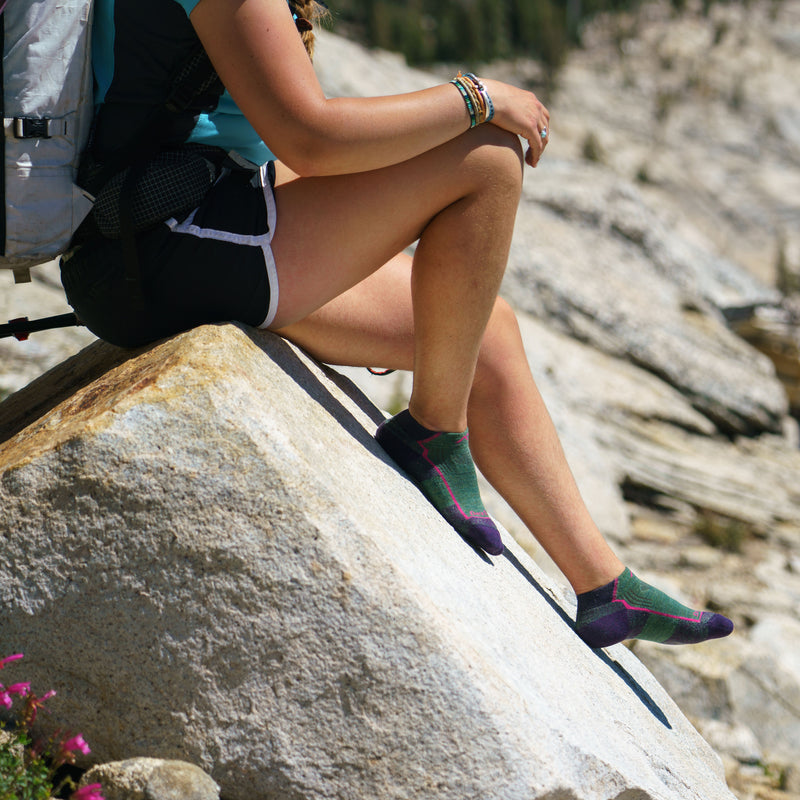 Image of a woman sitting on a rock, wearing shorts and a hiking backpack, barefoot with Women's Hiker No Show Lightweight Hiking Socks in Moss, Lifestyle Image
