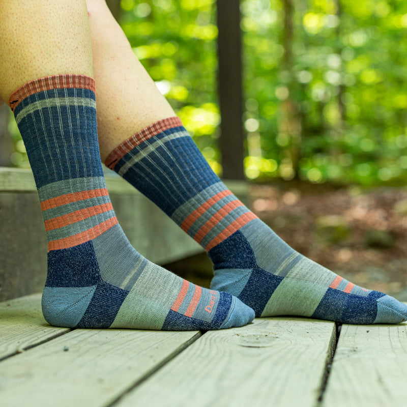 Close up image of a woman's feet outside, wearing Women's Her Spur Boot Lightweight Hiking Socks in Denim, Lifestyle Image
