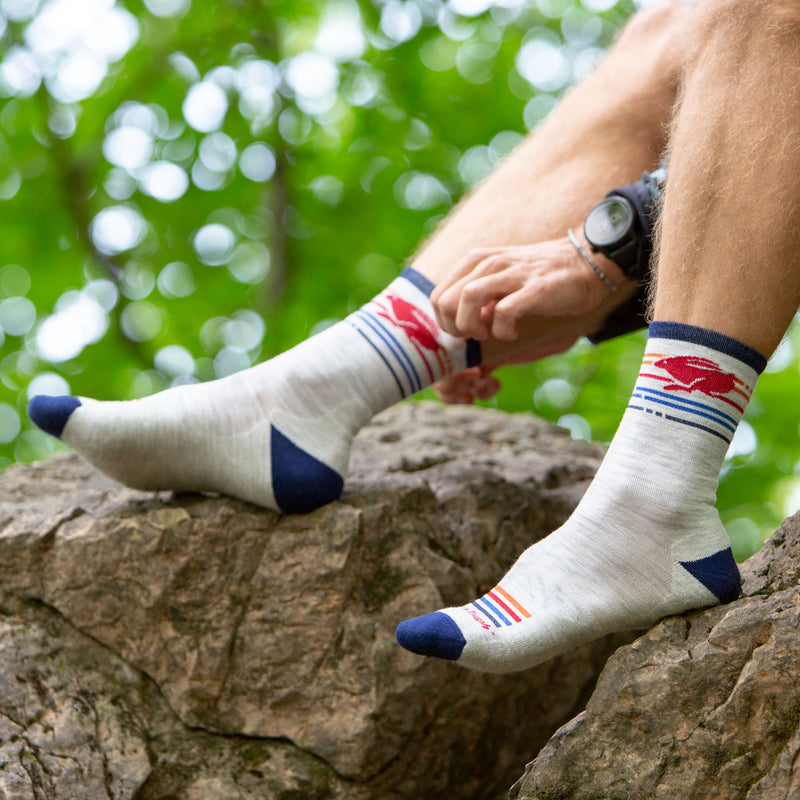 Close up lifestyle image of a man sitting on a rock barefoot wearing Pacer Micro Crew Ultra-Lightweight Running Sock in Ash, Lifestyle Image
