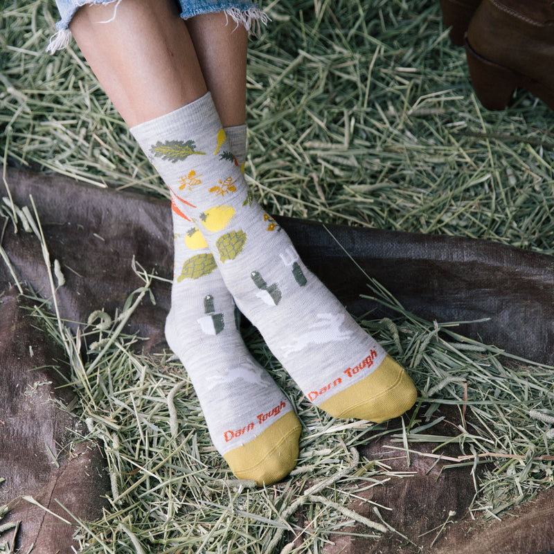 Close up image of a woman's feet, ankles crossed, resting on hay, wearing Women's Farmer's Market Crew Lightweight Lifestyle Socks in Ash, Lifestyle Image