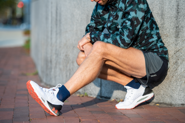 Lifestyle image of man squatting close to the ground, one leg outstretched, wearing running shorts, running sneakers and Run Quarter Ultra-Lightweight Running Socks in Baltic, Lifestyle Image