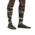 Image of a woman's legs on a white background wearing Women's Camo Over the Calf Midweight Ski & Snowboard socks in Forest