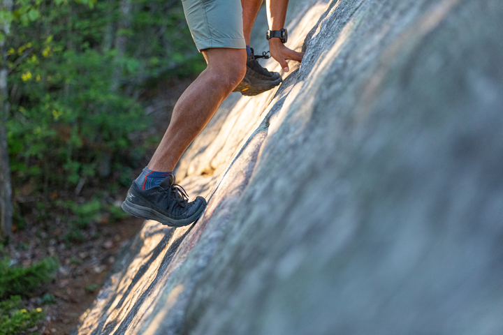 Close up image of a man's feet wearing shoes and Men's Light Hiker No Show Hiking Socks as he climbs a rock face, Lifestyle Image