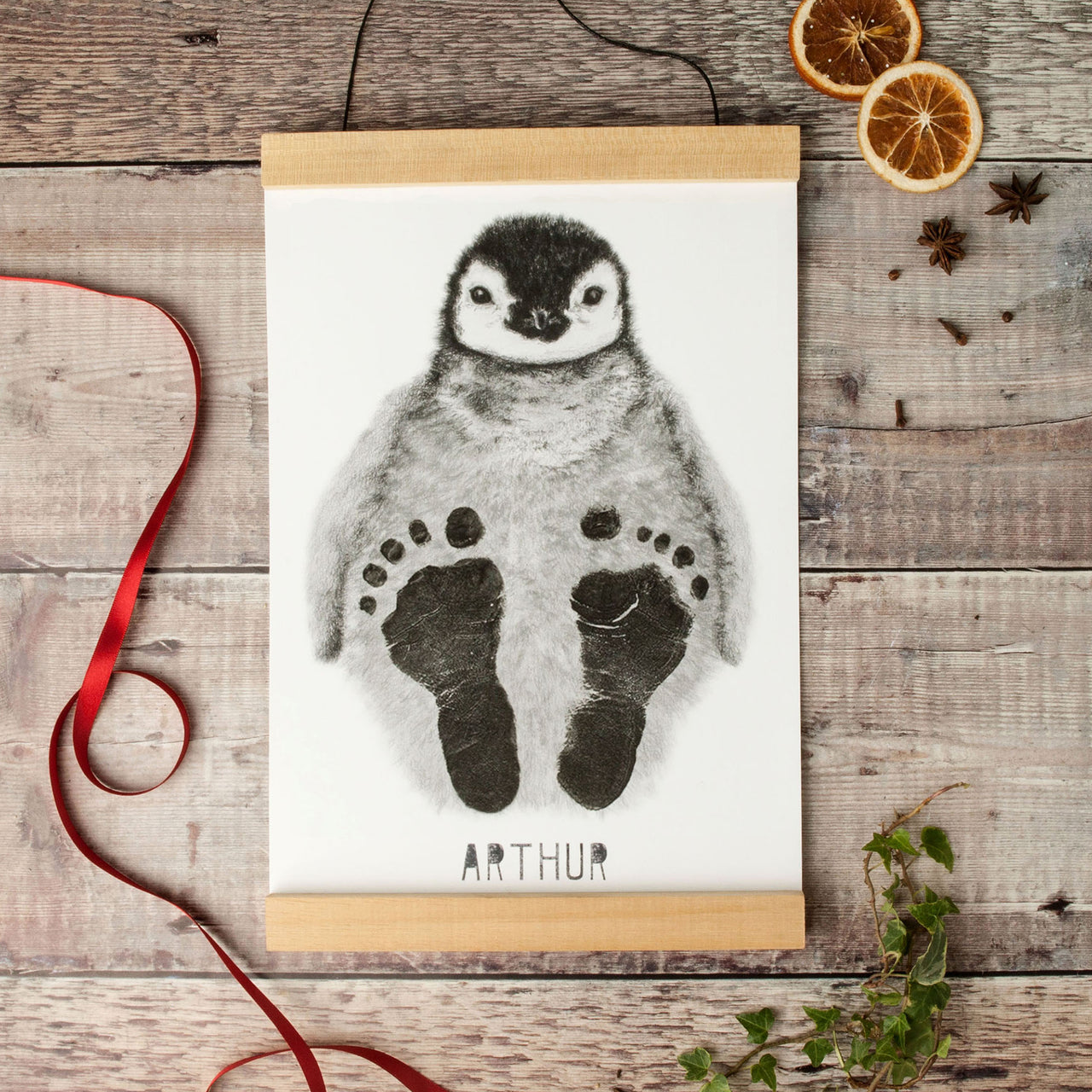 Baby penguin footprint kit for Christmas with orange and red ribbons