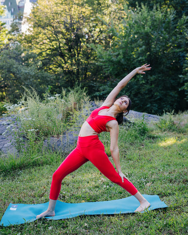 Kim Levin Fit Model red yoga reverse warrior pose in Central Park