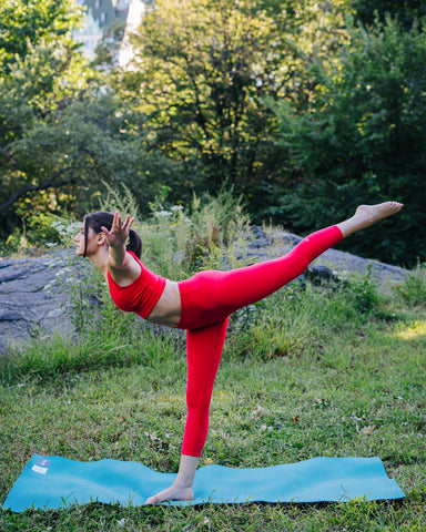 Kim Levin Fit Model red yoga arabesque pose in Central Park