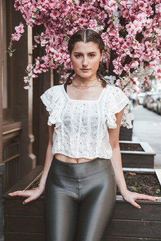 Kim Levin Fit Model in a white blouse and biker shorts with flowers in SoHo, NYC.