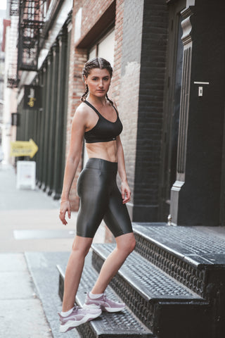 Kim Levin Fit Model black sports bra and biker shorts doing an Achilles heel stretch in SoHo, NYC.