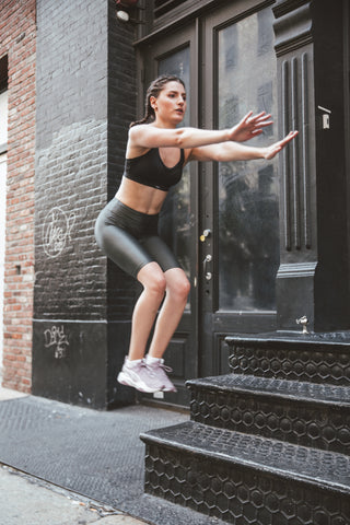 Kim Levin Fit Model in a black sports bra and biker shorts jumping in SoHo, NYC.
