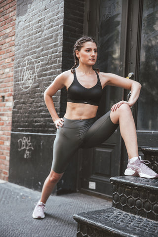 Kim Levin Fit Model in a black sports bra and biker shorts stretching in SoHo, NYC.