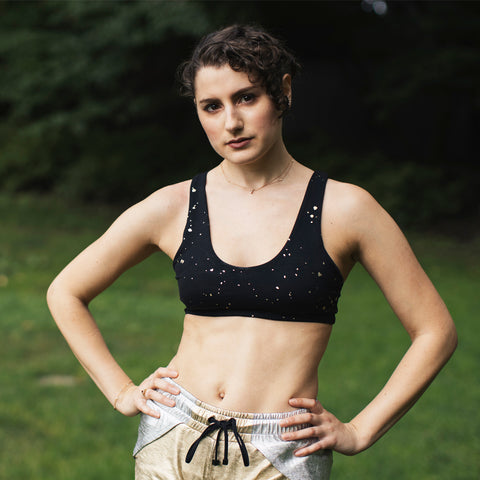 Kim Levin Fit Model in a black sports bra and gold shorts for a headshot portrait in Central Park
